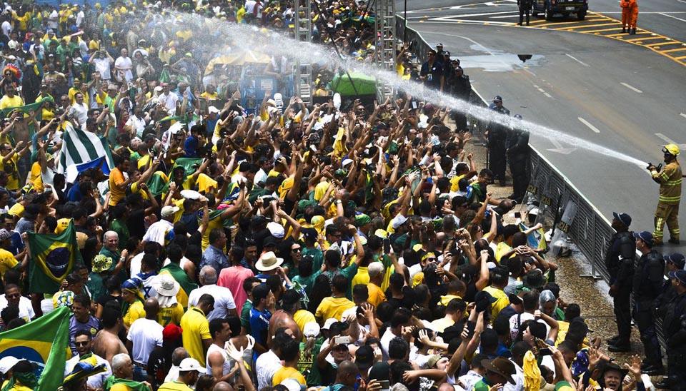 Bombeiros usam jatos de água para refrescar o público que aguarda a cerimônia de posse de Bolsonaro, na Praça dos três Poderes