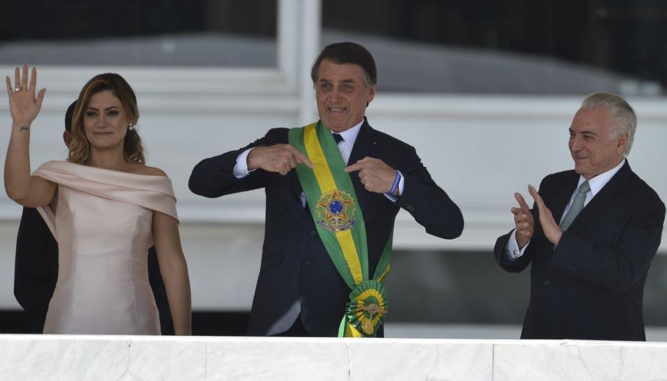Jair Bolsonaro e Michelle Bolsonaro exibem a faixa presidencial