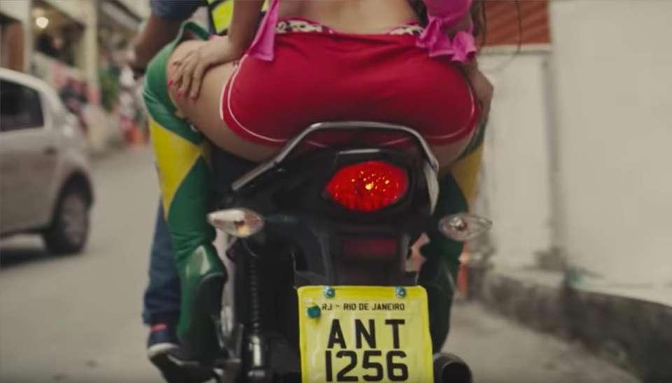 Anitta começa o clipe fazendo mistério. Andando de costas e exibindo o bumbum natural com um shortinho vermelho