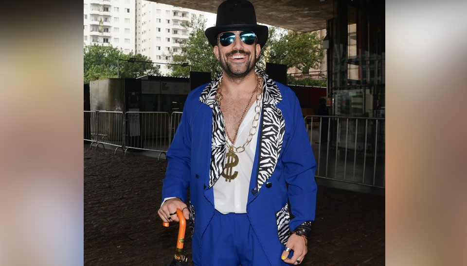 O sírio estava no estilo com um terno azul royal, chapéu, óculos escuros (apesar da ausência de Sol) e um baita colar com um cifrão no peito