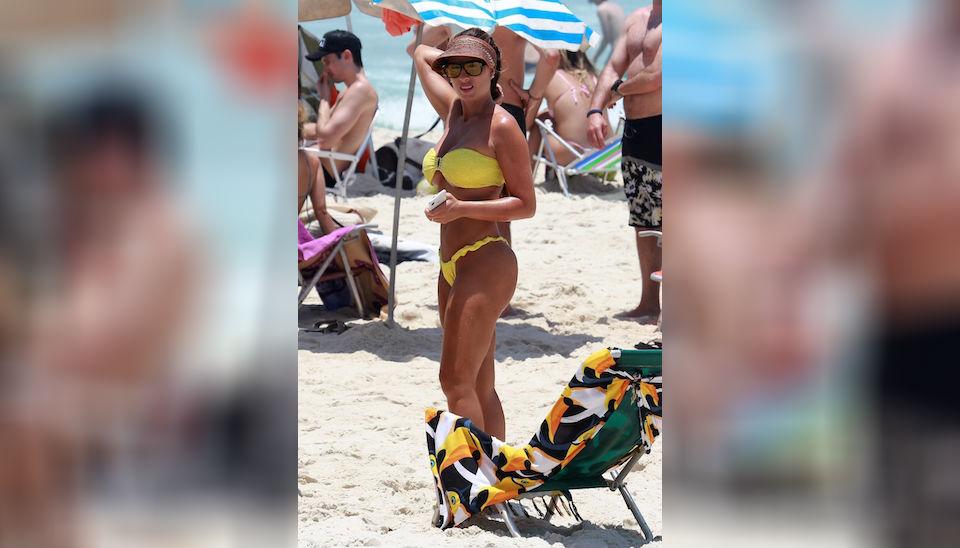 Recém-casada, Nicole Bahls evidenciou o bronzeado com biquíni amarelo em dia de praia na Barra da Tijuca, no RJ. Mas a musa quase mostrou demais com o modelo tomara que caia
