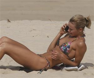 Renata Kuerten faz exercícios e se bronzeia em praia do Rio de Janeiro