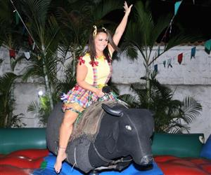 Com saia curta, Viviane Araújo tenta se equilibrar sobre touro mecânico em arraiá