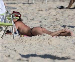 Luiza Tomé deita de bumbum para cima e desamarra biquíni para tomar sol em praia no RJ