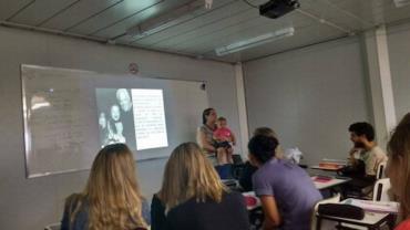 Professora segura bebê no colo para que a mãe possa prestar atenção na aula