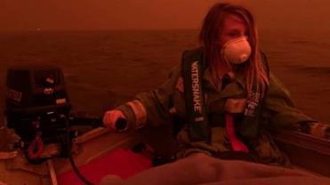 Mãe registra filho fugindo de barco de incêndio na Austrália