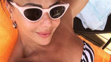 Após noite badalada, Viviane Araújo relaxa e se bronzeia com biquíni listrado