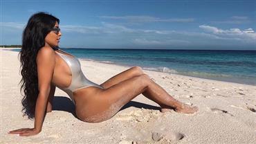 Kim Kardashian posa de maiô cavado e exibe curvas em praia