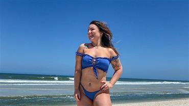 """Ex-BBB Maria Claudia posa de biquíni em praia e fã elogia: """"Sereia fora do mar"""""""