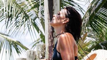 Carolina Ferraz se refresca em chuveiro e corpo bronzeado chama a atenção